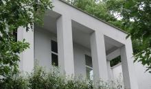 Witte crepi voor een alleenstaande woning in een bosrijke omgeving